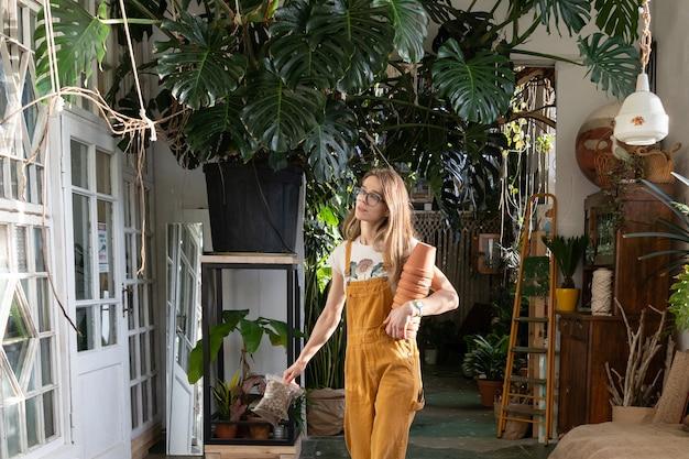 Vrouwelijke bloemist draagt bloempotten van klei voor het herplanten van kamerplanten in de binnentuin
