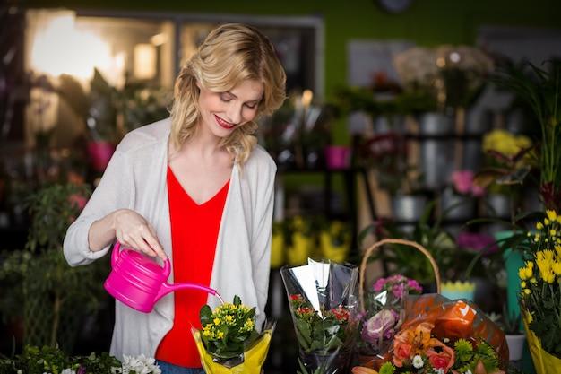 Vrouwelijke bloemist drenken bloemen