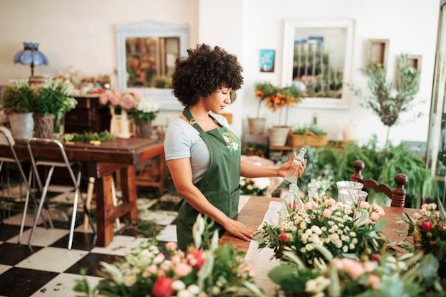 Vrouwelijke bloemist houden glazen fles in de winkel