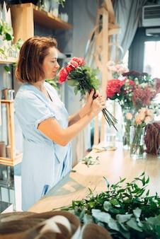Vrouwelijke bloemist houdt verse rode rozen bloemenwinkel. bloemisterij, boeketten maken
