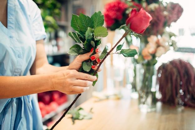 Vrouwelijke bloemist houdt verse rode rozen bloemenwinkel