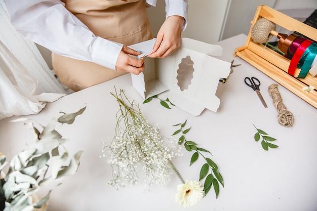 Vrouwelijke bloemist maakt een witte papieren geschenkdoos op haar bureau in een bloemenwinkel