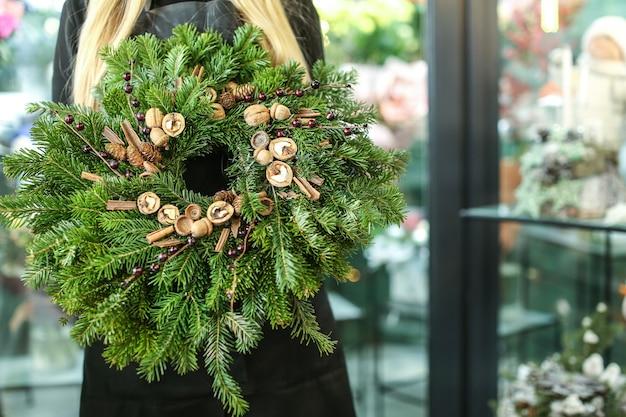 Vrouwelijke bloemist met kerstkrans in bloemenwinkel
