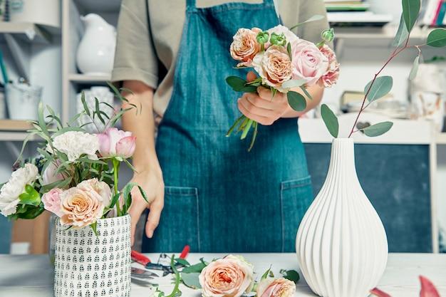 Vrouwelijke bloemist ongericht in bloemenwinkel maken mooie kunstmatige boeket. een leraar bloemsierkunst in masterclasses of cursussen. professionele, bloemen- en decoratiestudio. kopieer ruimte voor ontwerp