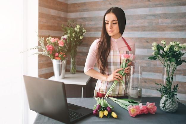 Vrouwelijke bloemist op het werk: vrij jonge donkerharige vrouw mode modern boeket van verschillende bloemen maken. vrouwen die met bloemen in workshop werken. ze gebruikt de laptop op het werk