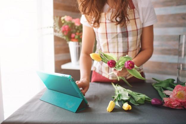 Vrouwelijke bloemist op het werk: vrij jonge donkerharige vrouw mode modern boeket van verschillende bloemen maken. vrouwen die met bloemen in workshop werken. ze gebruikt de tablet op het werk.