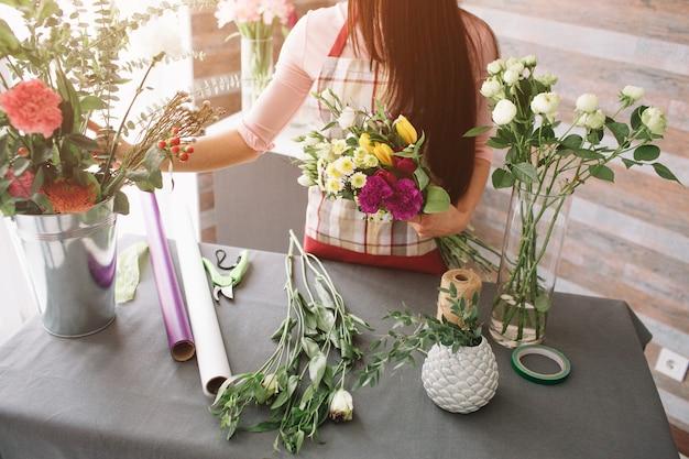 Vrouwelijke bloemist op het werk: vrij jonge donkerharige vrouw mode modern boeket van verschillende bloemen maken. vrouwen die met bloemen in workshop werken