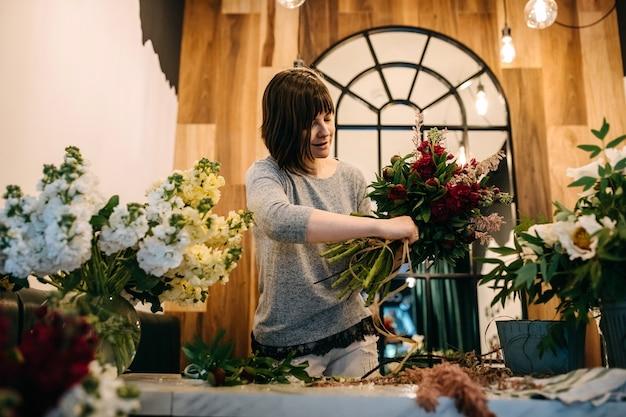Vrouwelijke bloemist paars lila boeket maken bij bloemenwinkel