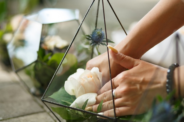 Vrouwelijke bloemist zet verse succulente en roze bloemen in florarium van glas