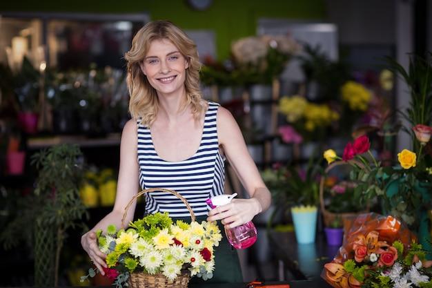 Vrouwelijke bloemisten die water bespuiten op bloemen in bloemenwinkel