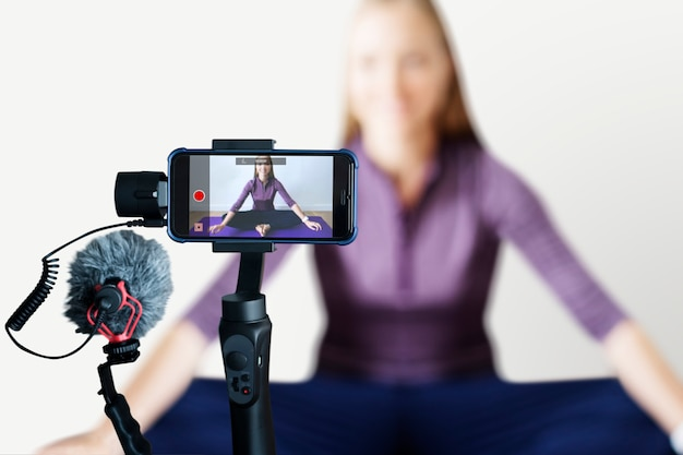 Vrouwelijke blogger die een online yogales streamt