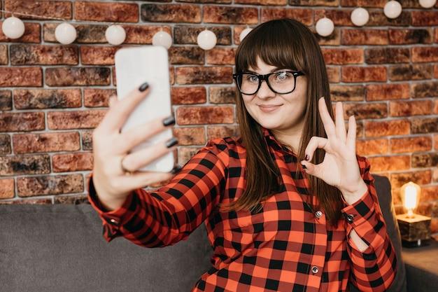 Vrouwelijke blogger die online met smartphone streamt en goed teken geeft