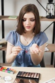 Vrouwelijke blogger die theatrale make-up op pallet probeert
