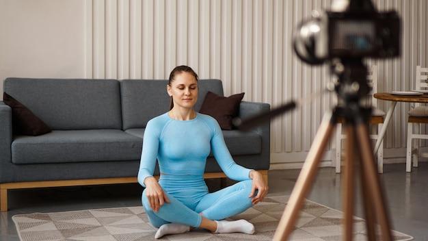 Vrouwelijke blogger die thuis sportvideo opneemt. een vrouw in een yogahouding neemt video op voor een online cursus. thuis sporten in je eentje.
