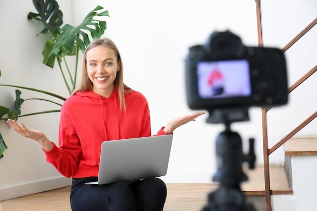 Vrouwelijke blogger die video binnenshuis opneemt
