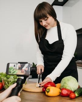 Vrouwelijke blogger die zichzelf opneemt terwijl ze een salade met groenten klaarmaakt
