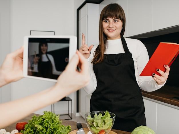Vrouwelijke blogger die zichzelf opneemt tijdens het voorbereiden van salade en het lezen van boek