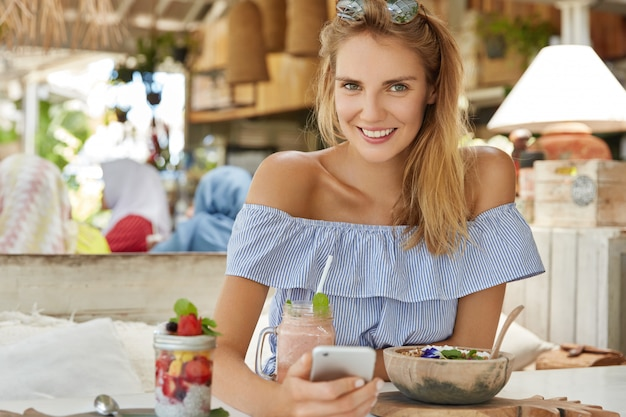 Vrouwelijke blogger recreëert tijdens zomervakanties in gezellig restaurant, sms-bericht naar volgers op persoonlijke website