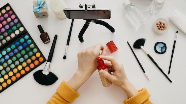 Vrouwelijke blogger streaming make-up foundation online met smartphone