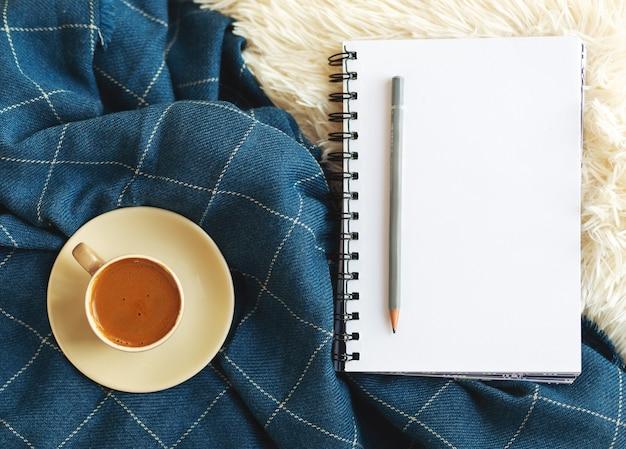 Vrouwelijke blogger-tafelwerkplek met spiraalvormig notitieboekje voor takenplanner en koffie op pluizige witte omslag en blauwe deken. mockup met kopieerruimte. bovenaanzicht