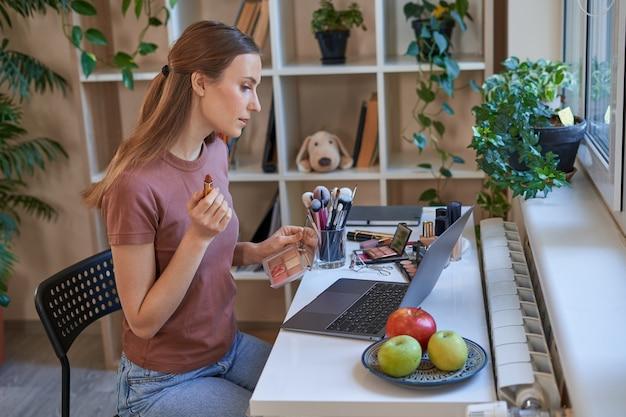 Vrouwelijke blogger tijdens online make-up tutorials thuis