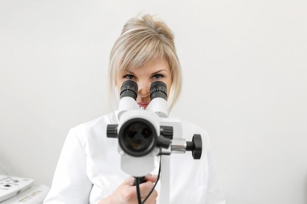 Vrouwelijke blonde arts gynaecoloog kijkt door een colposcoop