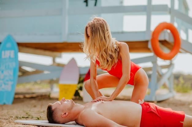 Vrouwelijke blonde badmeester in rode bikini die jonge man op het strand redt