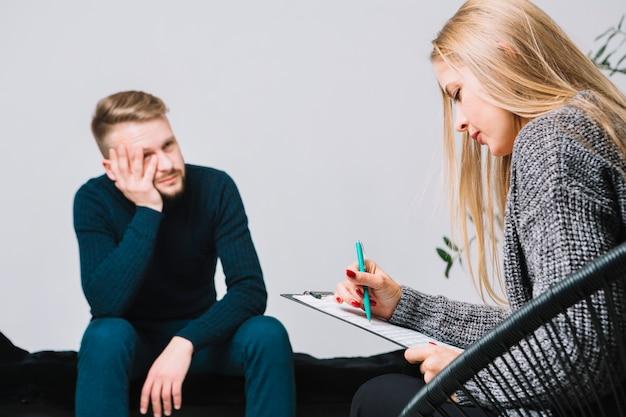 Vrouwelijke blonde jonge psycholoog die een mannelijke cliënt raadpleegt tijdens besprekingstherapie