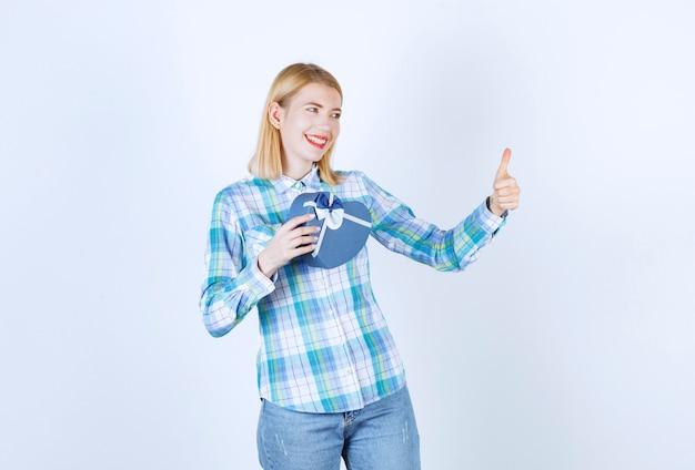 Vrouwelijke blondine maakt handteken terwijl ze de gestreepte zak vasthoudt en naar haar rechterzijde leunt