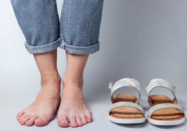 Vrouwelijke blote voeten in jeans en sandalen op wit.