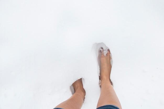 Vrouwelijke blote voeten op een ijzige winterdag in een sneeuwjacht