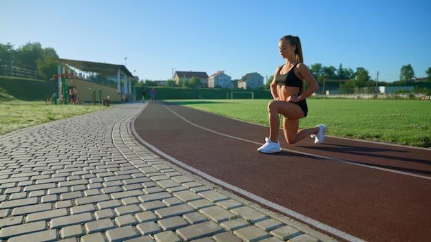 Vrouwelijke bodybuilder die lunges oefent in het stadion