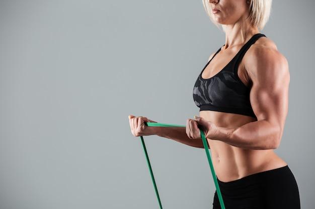 Vrouwelijke bodybuilder die zich uitstrekt met elastisch rubber