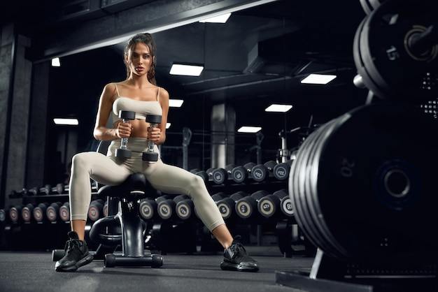 Vrouwelijke bodybuilder training met halters.