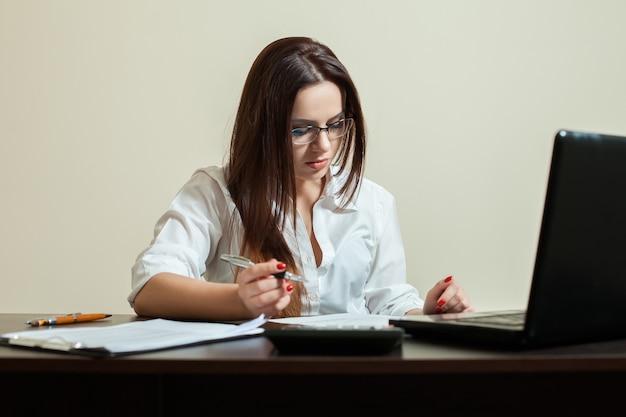 Vrouwelijke boekhouder in glazen met behulp van laptop