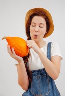 Vrouwelijke boer controleert de herfstoogst van pompoenen op rijpheidsconcept van landbouw