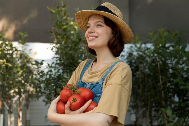 Vrouwelijke boer die wat tomaten vasthoudt