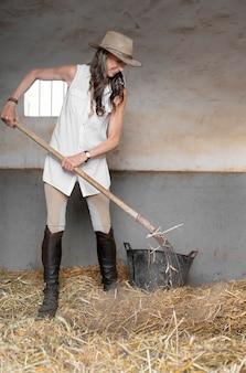 Vrouwelijke boer hooi uit paardenstallen schoonmaken