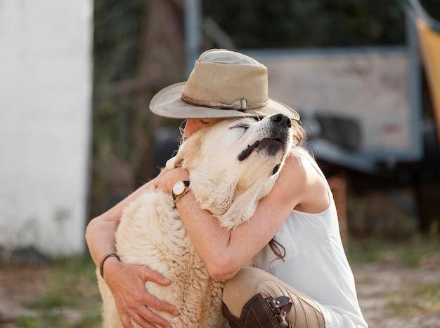 Vrouwelijke boer omarmen haar boerderijhond