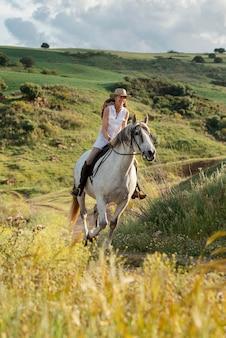 Vrouwelijke boer paardrijden buiten in de natuur