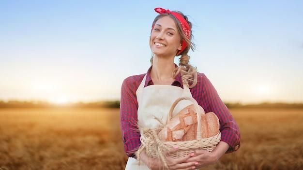 Vrouwelijke boer staande tarwe landbouwgebied vrouw bakker bedrijf rieten mand brood product