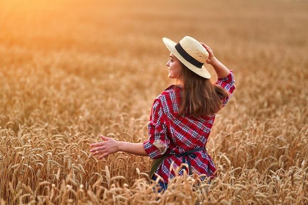 Vrouwelijke boer staat alleen tijdens het wandelen door een geel veld van droge rijpe tarwe tussen gouden aartjes bij zonsondergang