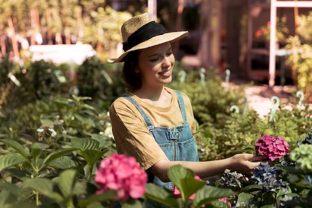 Vrouwelijke boer werkt alleen in haar kas