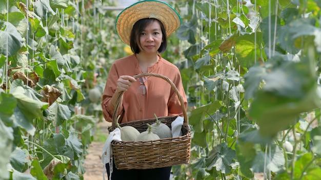 Vrouwelijke boeren die meloenmanden vervoeren om zich voor te bereiden op levering aan klanten.