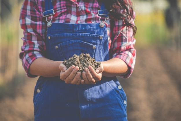 Vrouwelijke boeren onderzoeken de bodem.