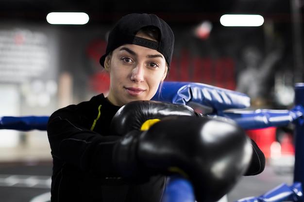 Vrouwelijke bokser die en in de ring met beschermende handschoenen glimlacht stelt