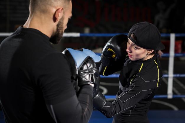 Vrouwelijke bokser in de ring training met beschermende handschoenen