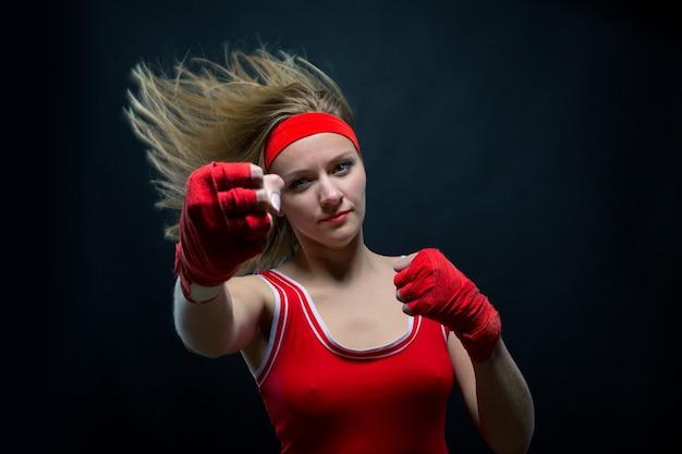 Vrouwelijke bokser in rode boksbandages en sportkleding