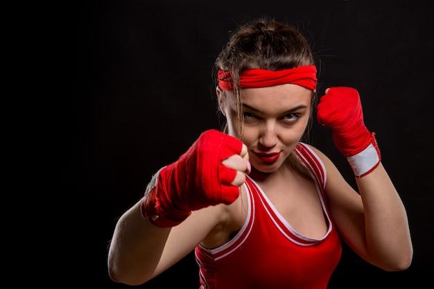 Vrouwelijke bokser in rode handschoenen en sportkleding op bokstraining. vrouw vechter op zwarte achtergrond