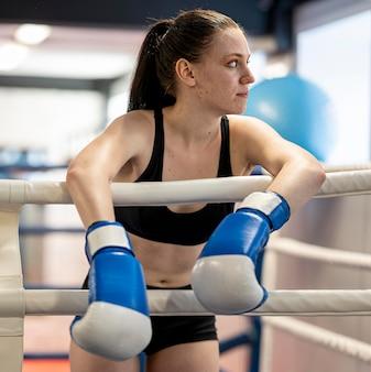 Vrouwelijke bokser met beschermende handschoenen in de ring